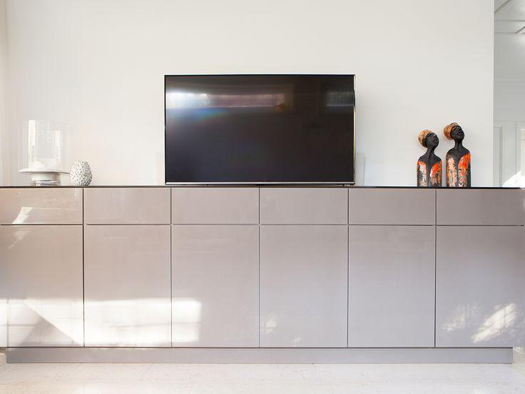 Het tv-dressoir is gemaakt van HDF, hoogglans gespoten. Op het meubel ligt een gekleurde glasplaat. Het tv-dressoir is voorzien van een tv-lift.