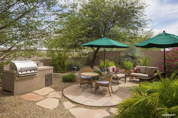 Southwestern Patio with Outdoor kitchen, Flagstone - Arizona Buff, Fence, Round Crank Patio Umbrella - Green 9', Raised beds