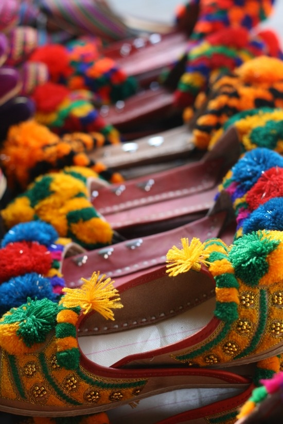 Colorful Khussas, Lahore, Pakistan. Khussas are made by artisans mostly using vegetable-tanned leather. The uppers are made of one piece of leather or textile embroidered and embellished with brass nails, cowry shells, mirrors, bells and ceramic beads. Even the bonding from the upper to the sole is done by cotton thread that is not only eco-friendly but also enmeshes the leather fibers with great strength.