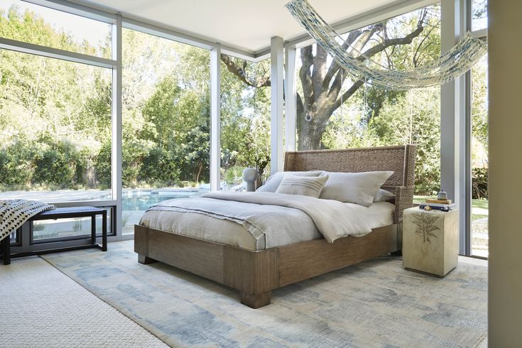 The Cesta Bed is a stately silhouette in mixed materials for a look that is at once elegant and informal. The sheltered, sculptural piece features an expertly hand-carved wooden base cadenced by vertical lines. The headboard is swathed in a grey raffia and Danish cord herringbone weave for textural interest.