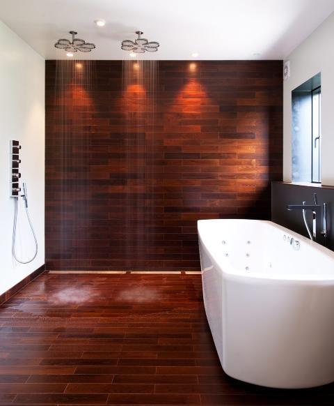 VÅTROMSPARKETT PÅ GULV OG DUSJVEGG: Parketten heter Termoask badegulv, og er varmebehandlet for å tåle det fuktige miljøet. Gulvet er levert av Moelven. Badekaret er fra Westerbergs, og armaturene fra Hansgrohe. FOTO: Espen Grønli