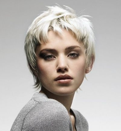Short, platinum blonde hair is given sexy layering and feathers in this pixie crop. Hairstyles like this are basically wash 'n wear because of the superb and classic cut. Edges are unevenly feathered, and a high fringe has tufts deeply feathered and lazily arranged across the forehead.The layers on top give height to the short hair, while flirty ends fly away from the nape.