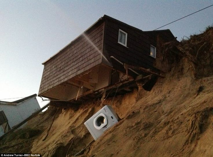 Devastated residents watched their cliff-top homes disappear into the sea as last night's tidal surge hit the east coast of Britain.