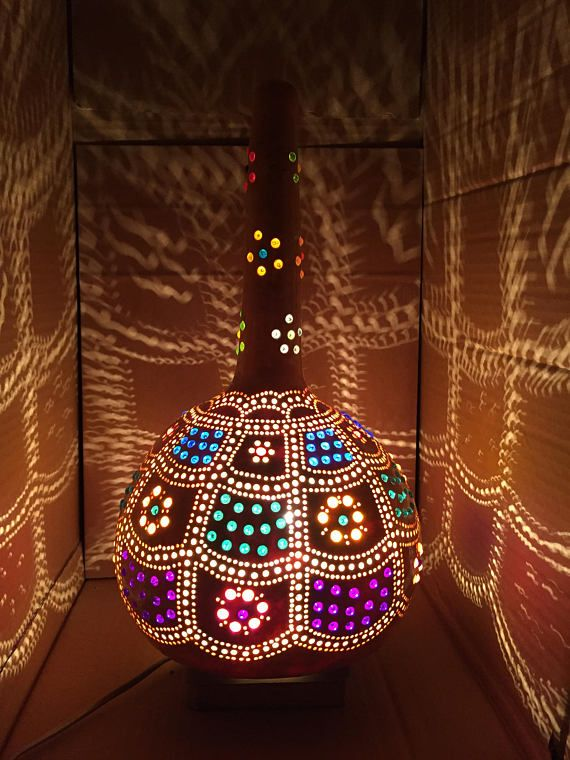 The original ornament of this authentic turkish gourd covers its surface like a golden net.  This shiny lamp is made of a natural bottle gourd from the Aegean coast of Turkey. The gourd was dryed and thoroughly cleaned. Hundreds of the holes on the surface of the lamp were made with different diameter drills (2mm, 3.5mm and 6 mm). Each of colorful round beads was carefully placed by hand.  The net is painted golden color by acrylic paint. Except this the turkish lamp has its natural colour…