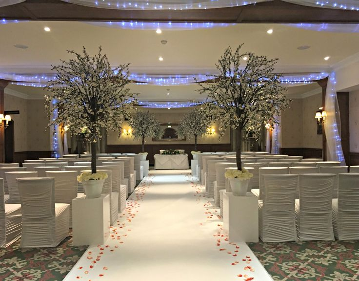 Wedding Ceremony Set-Up with blossom trees, white chair covers, white carpet and rose petals along the isle at Ashdown Park Hotel.