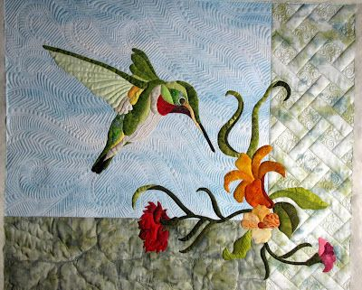 Sparky the hummingbird - quilting in blue to look like movement, gray at the bottom to look like a rock wall & white on the sides to look like a trellis.