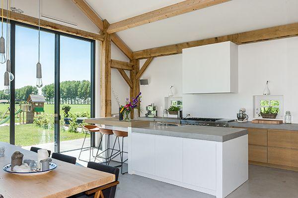 [ Kitchen with an amazing view ]  Deze strakke witte keuken is gerealiseerd door interieurbouwer Oock. Het stoere fornuis Westalls kochten de bewoners bij BOS fornuizen. Keukenapparatuur van KitchenAid maakt het professionele plaatje compleet. Het keukenblad is van Mortex.  #keuken #kitchen #wit #white #Oock #Westalls #BOSfornuizen #KitchenAid #Mortex #interieurdesign #interiordesign #hout #balken #wood #historie #historical