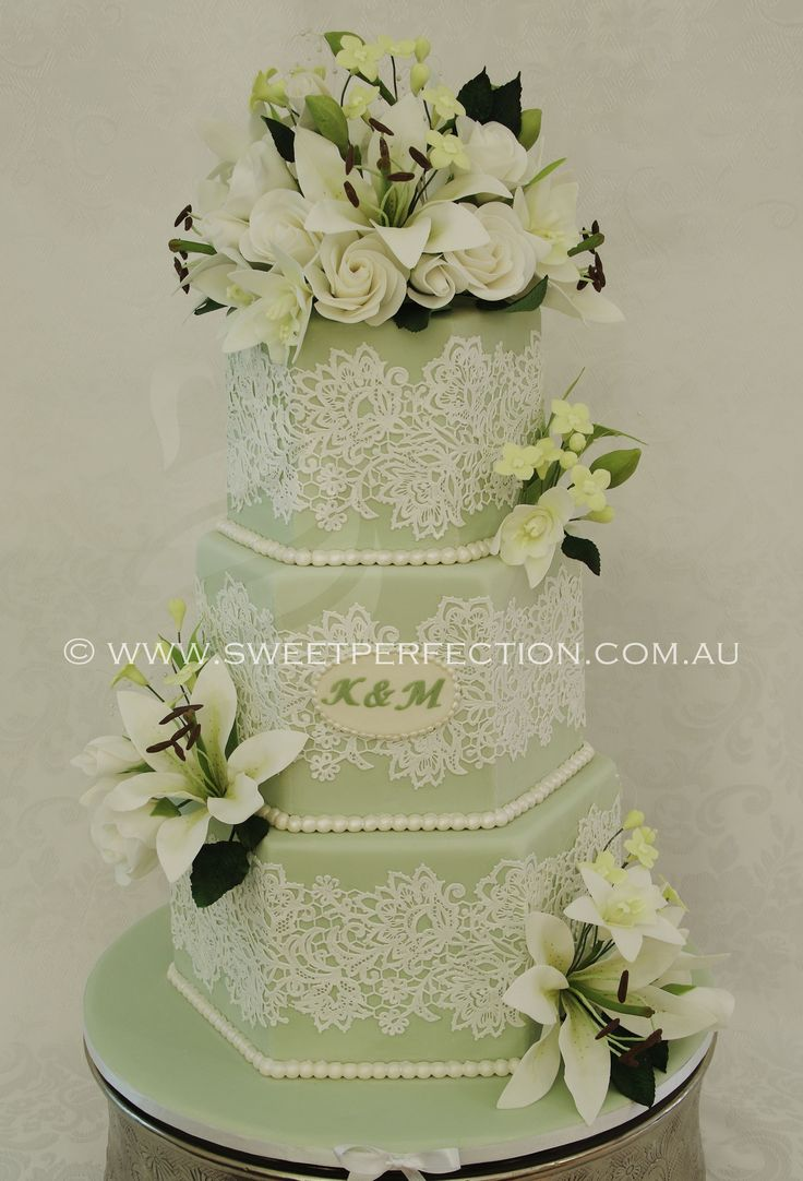 Mint green hexagonal wedding cake with edible lace and all sugar flowers. Custom design by Sweet Perfection.