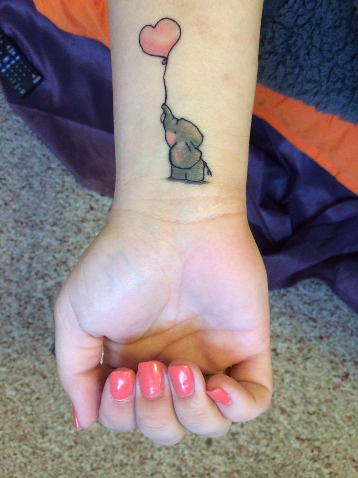 Chica con un tatuaje en la muñeca de un elefante sosteniendo un globo con la trompa