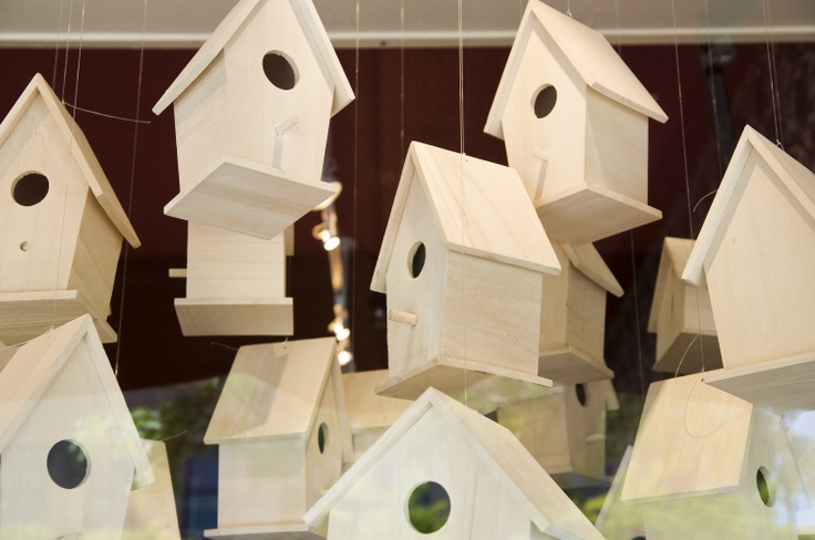 Birdhouses hang in a shop on North Higgins Avenue in