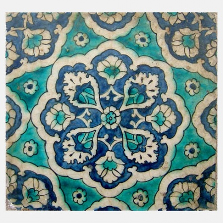 DAMASCUS TILE . . . . . . . . . . . . . . . . . . . . . . . . . . . . . Syria, 17th century 24 x 24 cm A stone paste square tile painted in underglaze cobalt blue, emerald green, turquoise and manganese purple. Outlined in black, a central blue boss containing white cartouches around a central rosette, all contained within a surrounding array of triangular sections containing flowers and rosettes.