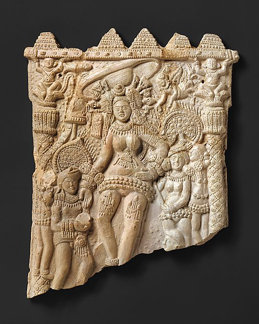1st C. BCE. Shunga period. Goddess and Attendants. Many molded plaques, this the largest, were found at the ancient city in Bengal - Chandraketugarh. Likely  icons for personal devotion. All are dominated by a large naked heavily bejeweled female. The honorific umbrella, the lowered hand gesturing the grant of boons, suggests she is a deity. In this early phase, she routinely appears with weapons projecting from her headdress, a form later seen with Durga. India