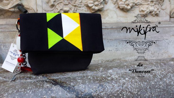Pochette Trinacria: Mini Bag in cotone nero e cotone colorato a fantasia triangolare. Manichetto gioiello con ceramiche colorate, nappina rossa, ciondolo chiave e catena nera.