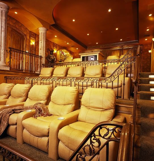 Dramatically-tiered Home Theater with iron and brass railings...