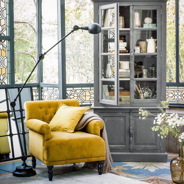 Dans ce coin de salon, aux côtés d'un imposant fauteuil jaune moutarde, un énorme vaisselier à la patine apparente renferme une collection de vaisselle ancienne.