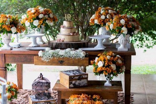 Mesa de bolo rustica  elementos :   Vasos de porcelana baixos  Mesa de madeira de demolição  suportes de doces em louça gaiola de ferro envelhecida   cascalho de pinus polido no chão  flores usadas: (rosas brancas, alstroemérias laranja, margaridas laranja)