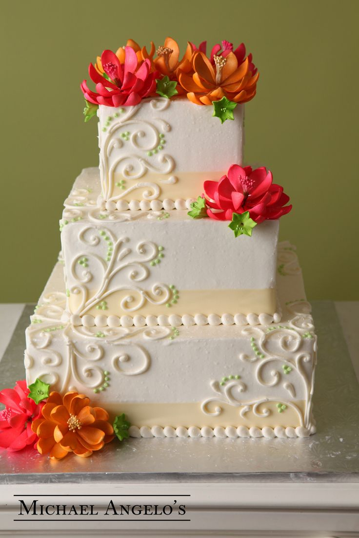 Orange Lotus #76Ribbons This ivory buttercream cake is accented with matching ribbon and swirls with a pop of color from the gum paste lotus flowers.