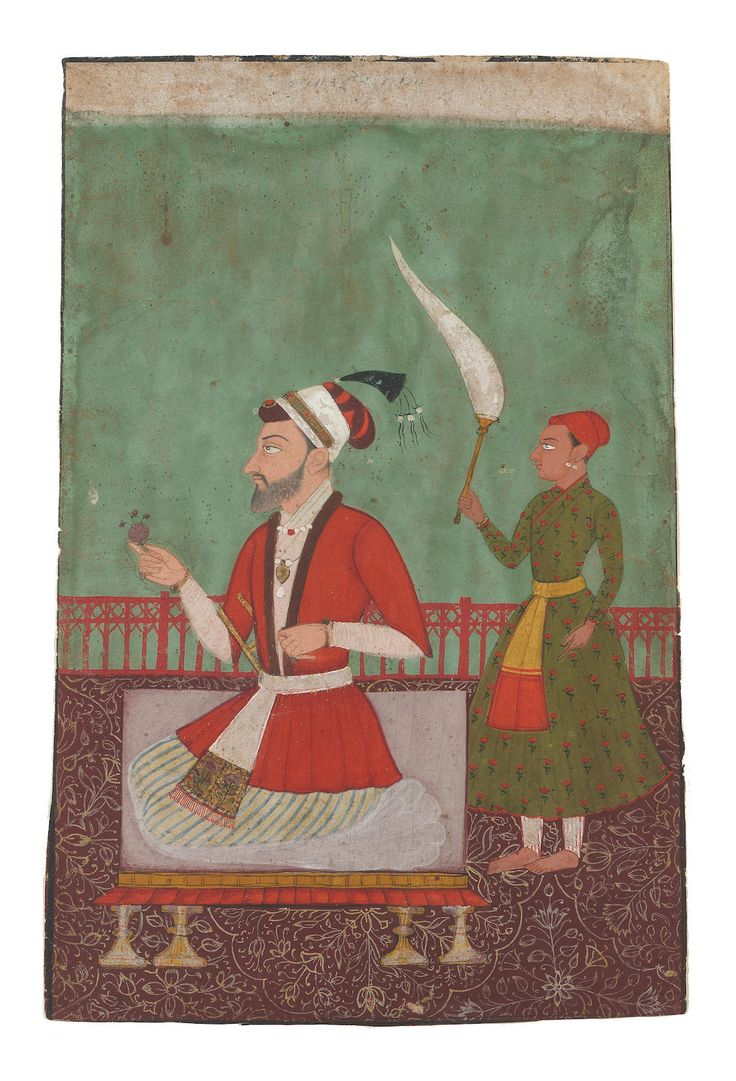 Aurangzeb on a terrace, kneeling on a dais on a floral carpet, holding a flower in his hand, whilst an attendant stands behind holding a fly-whisk