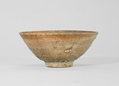 井戸茶碗 銘 奈良 - 出光コレクション - 出光美術館 朝鮮 朝鮮王朝時代 大ぶりで素直な姿をもつ井戸茶碗で、なだらかに立ち上がりながら、胴にわずかなふくらみを含んでいる。裾には一段の削りをめぐらせ、高台がつく。灰褐色の粗い土の上からかかる灰白釉は、裾から高台にかけて、梅皮花(かいらぎ)と呼ばれる釉の縮みを生じており、井戸茶碗独特の、変化に富んだ質感をあらわす。釉色は落ち着いた紅茶色で、高台畳付は、釉がかからず露胎となっている。