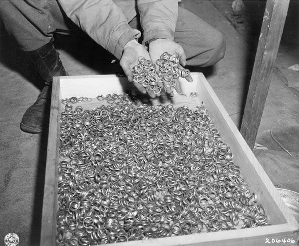 """""""A few of the thousands of wedding rings the Germans removed from their victims to salvage the gold. U.S. troops found rings, watches, precious stones, eyeglasses, and gold fillings, near Buchenwald concentration camp."""" By T4c. Roberts, May 5, 1945"""