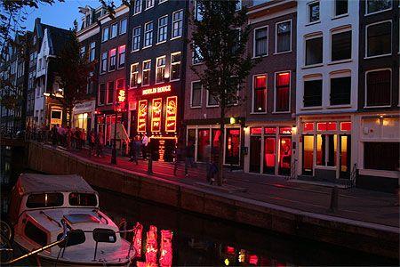 """Amsterdam > Centre d'Amsterdam > Quartier rouge Le quartier rouge débute à 50 m de la gare. Ses axes principaux sont Warmoesstraat, Oudezijds Voorburgwal et Oudezijds Achterburgwal et toutes les petites rues perpendiculaires, bien plus """"hard"""". Le long des canaux, dans les étroites ruelles, les fameuses « dames en vitrine » ont donné à ce quartier une renommée mondiale. Son nom vient des ampoules rouges qui éclairent les vitrines. Un quartier extrêmement touristique et fliqué."""
