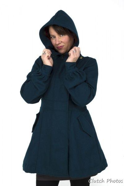 Mona kåpen, er en deilig, halv lang ull kåpe. Den er laget i lett ull og egner seg godt som vår/høst kåpe. Den er laget med høyt liv, som fremhever de kvinnelige