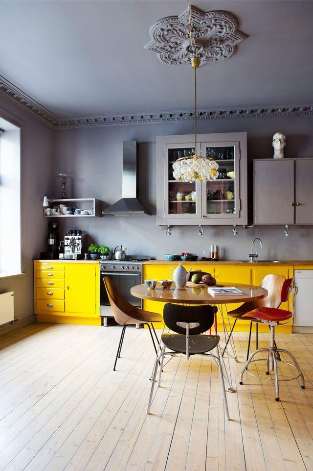 Cuisine avec une peinture grise chic qui contraste avec une teinte jaune vif, table en bois ronde et suspension déco