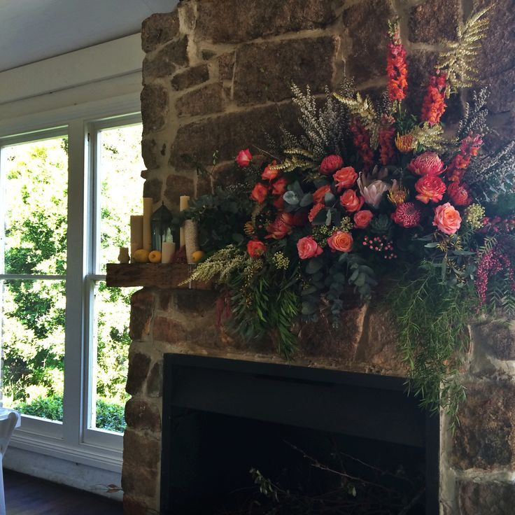 The fireplace floral centerpiece situated behind the bridal table.  { Sigrid + Luke }