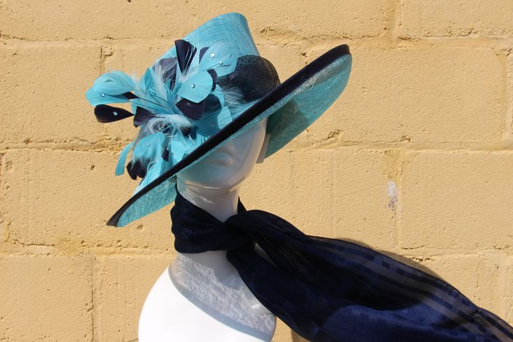 Brand new never been worn Jacques Vert occasion hats!  This aqua and navy blue occasion hat features a beautiful featherd corsage, navy trim and aqua loop detailing to complete the look. This statement hat is the perfect finishing touch for your special occasion outfit. Retails: $269   Sale Price: $69.30