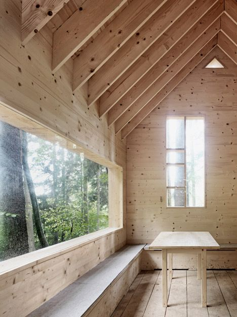 Openings in the walls of this wooden shelter create display compartments where children can show off treasures collected from the trails of the surrounding forest.
