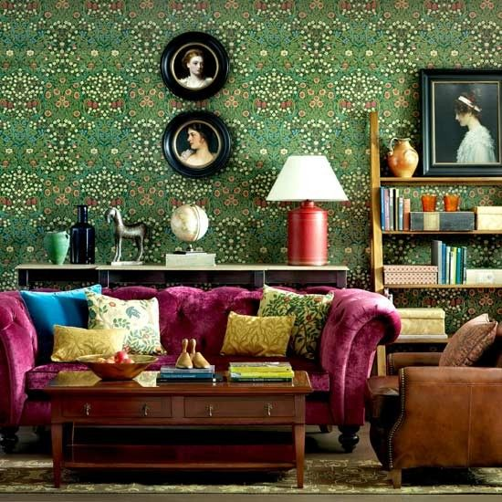 Vintage Sitting Room: A stunning room with a fuchsia, French Victorian style sofa and vintage-inspired wallpaper adorned with antique photos.