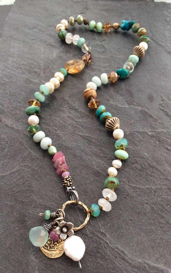 Colorful multi charm necklace by mollymoojewels. A mix of semi precious beads, including moonstones, pearls, turquoise, amazonite, jasper, raw ruby, sapphires and Czech glass in hues of blue, Aqua and pink. Adorned with sterling silver accents, a sterling flower charm, an artisan bronze replica of an ancient coin and wire wrapped briolettes The necklace is designed to fasten at the front with a sterling lobster clasp. Length is approx 21.5 including the charms. Packaged ready for giving…