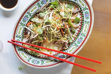 Salad of cabbage, mung beans sprouts and herbs with shredded duck