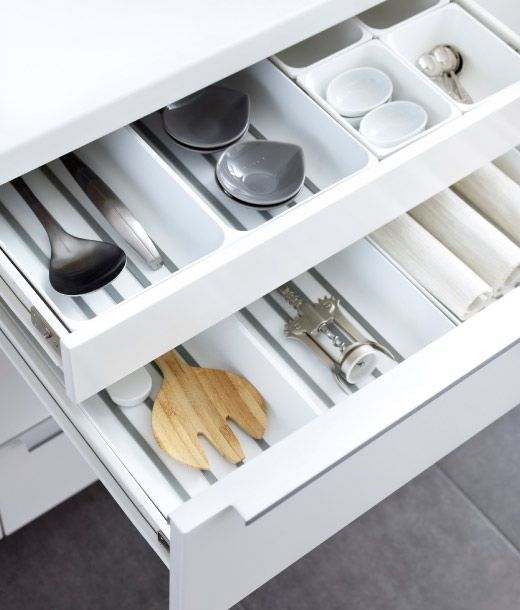 Open counter-level drawer revealing hidden cutlery drawer withwhite plastic organisers full of cutlery and utensils