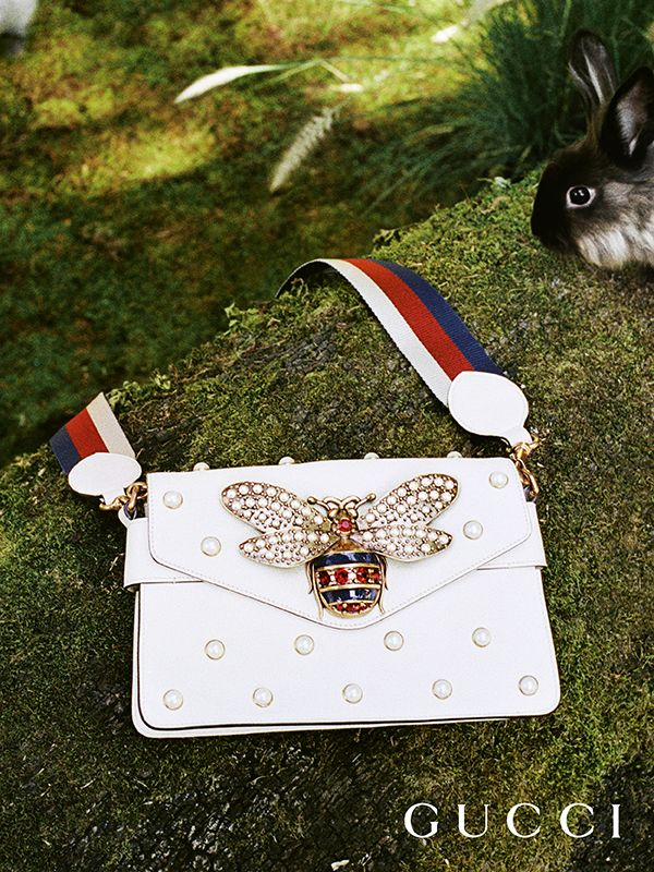 Discover more gifts from the Gucci Garden. A chain clutch decorated with pearl studs and an embellished bee by Alessandro Michele.