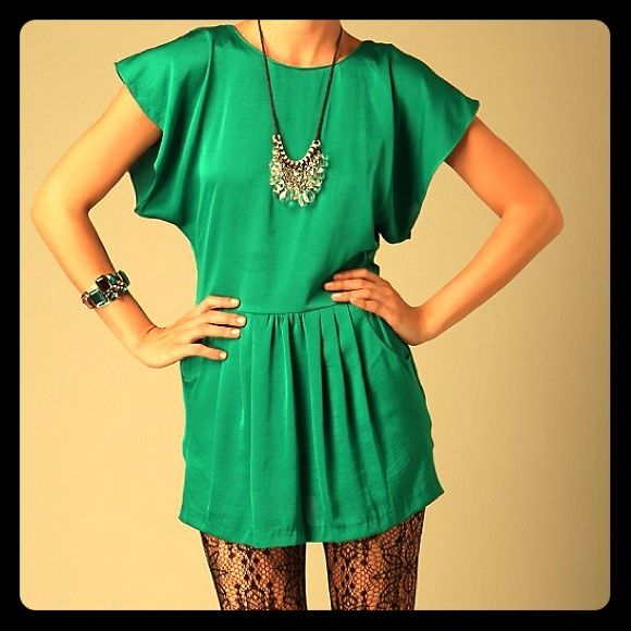 Free People Vintage Dynasty Tunic Dress in Emerald Silky woven shift dress/tunic in striking, luxe shade of green, perfect for spring summer! Versatile style to wear alone as dress or over skinny jeans or leggings for more casual look! Features batwing/ dolman sleeves, Pleating on the dropwaist and adorable front pockets!! With a sexy Open back  tie closure at the top. * Hidden center zip on the back. * 100% Polyester * Dry Clean * Imported * Measurements for Size Medium: Length: 31 3/...