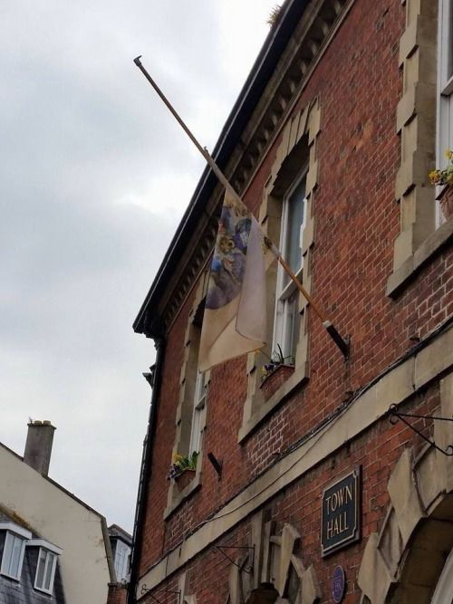 macpye:A little wind-whipped and weather-beaten today (well, it would be wouldn't it), the Ankh-Morpork flag flies at half mast from twin-town Wincanton's town hall…  [Source] aaaaw!!!