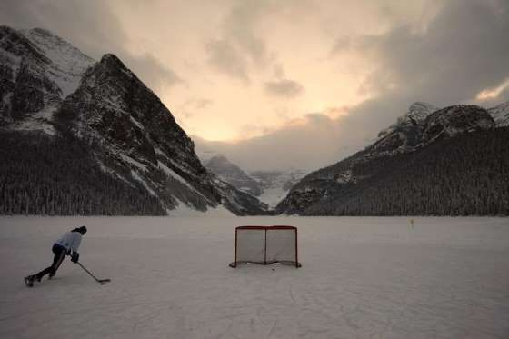 A hockey player skates on Lake Louise in the Canadian Rocky Mountains - REUTERS/Shaun Best
