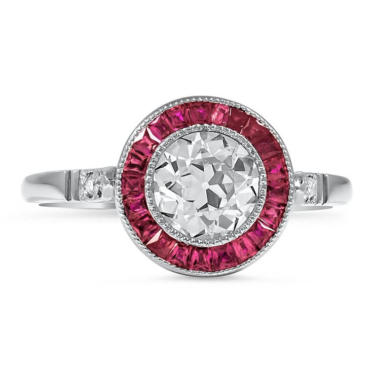 The Diedra Ring, top view. This gorgeous Art Deco reproduction piece features a bezel set old European cut diamond surrounded by a halo of twenty-one French cut natural ruby accents. Four round brilliant diamonds on the shoulders and a pierced gallery add to the alluring look of this ring (approx. 1.04 total carat weight).