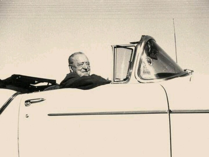 Mies smiling, uncharacteristically, in his yellow convertible!