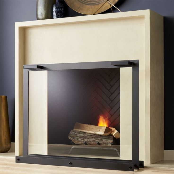 Shop Glass Fireplace Screen.  A window onto a cozy fire, our clean, modern fireplace screen frames in black-coated steel and a panel of tempered glass to protect and keep the view unobstructed.  The front handles add functionality to the sleek design.
