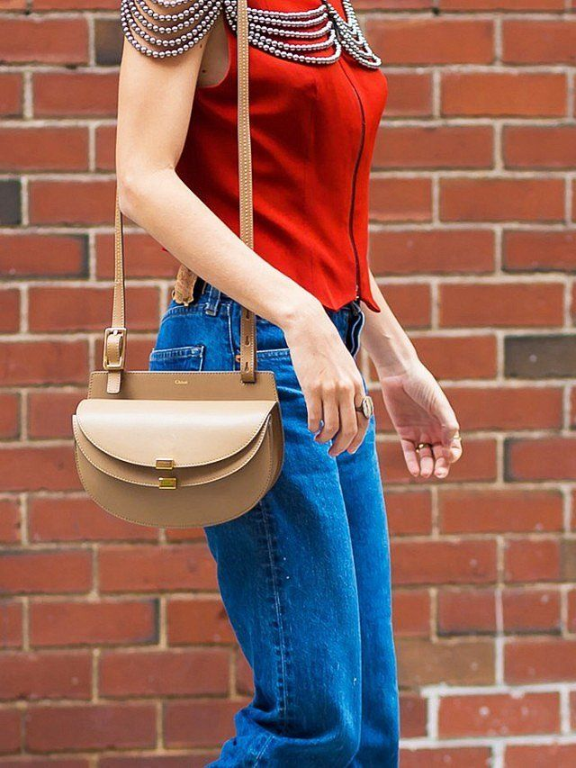 Boyfriend jeans paired with an embellished top and a neutral purse.