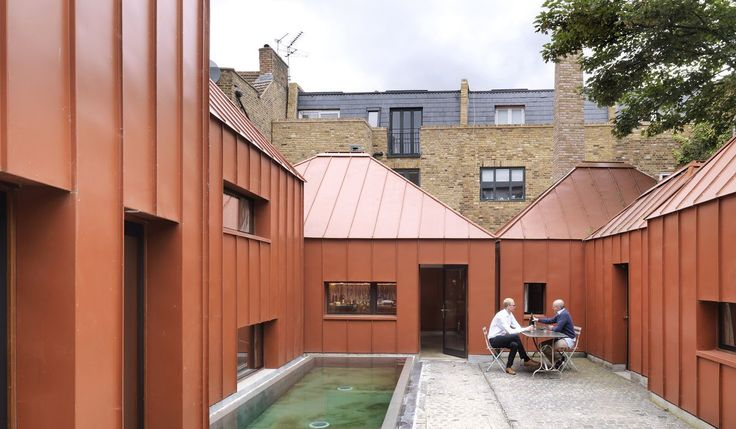 """Looking like something between a cluster of orange origami water bombs and a group of African huts, the most extraordinary """"house"""" has landed in a former breakers yard in Shepherd's Bush. Reached by an arched gateway and clad in burnt orange-coloured, polyurethane-coated, steel-based alloy — tin, to you and me — with attractive standing seams, this is the Tin House, the new home of architect Henning Stummel, 50, his wife Alice Dawson and their daughters, Justine Stummel, 16, Ayesha Dawson…"""