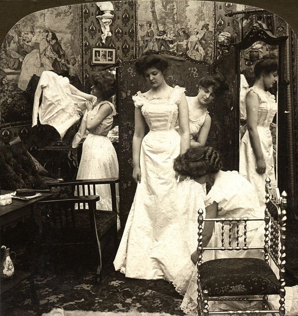 A rare behind the scenes glimpse of a rather serious looking Victorian bride who is being dressed for her big day.