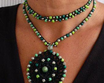 Este hermoso collar fue hecho a ganchillo con cuerda encerada beige/crudo, granos de cristal, cuentas de metal y plumas de plata tibetanas. Pueden ser usado cerca de la nuca o más flojo, solo apretado lo quieras. El encaje es suficiente para envolver 2 veces alrededor del cuello. Cada extremo de la cadena es cerrada por con algunas perlas de vidrio y una pluma de plata tibetana. It´s uno de un tipo y se ven muy bien en verano o en invierno.  Este collar de ganchillo es hecha por encargo y me…