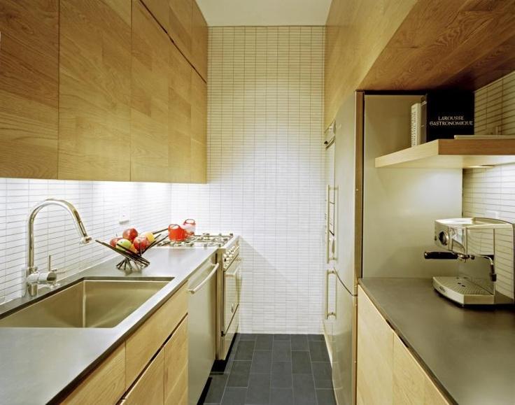 Kjøkkenet er smalt, men har til gjengjeld greit med benkeplass. Overskapene er uten håndtak og ser ut som rene paneler.
