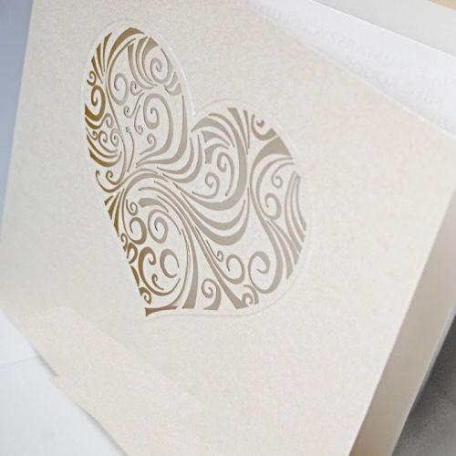 A meghívó kíváló minőségű ekrü dekoratív papírból készül.A borítón egy szív formájú lézerrel kivágott fantáziadús minta.A betétlap ekrü, matt felületű.       A meghívóhoz dekoratív boríték jár.A meghívóknál nincs szerkesztésiés nyomtatási költség