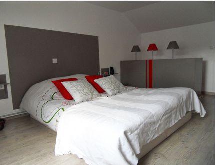 Deco chambre contemporaine. Lit drap et taie brodés blanc. coussins couleur rouge assortis aux lampes de chevet rouge