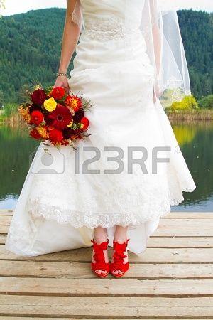 Een bruid draagt haar mooie rode bruiloft schoenen op haar trouwdag. Ze zijn stiletto's van levendige kleuren. Stockfoto - 16947236