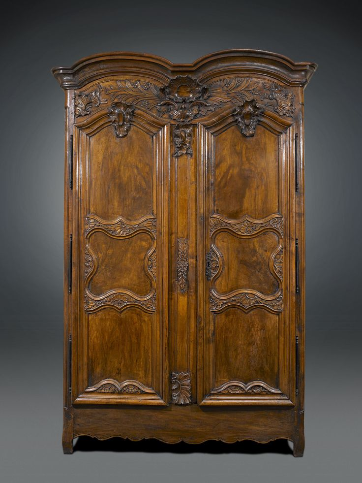 French Provincial Double Door Armoire, Late 18th Century - This majestic French walnut armoire is a stunning example of the Provencial style. Standing nearly nine feet high, this rare armoire featuring splendid rocaille carvings above its double doors and a wonderfully rich patina. Original mountings, double bolt locking mechanism and large key characterize this brilliant 18th-century furnishing. The first armoires appeared in France during the latter half of the 17th century and were most…